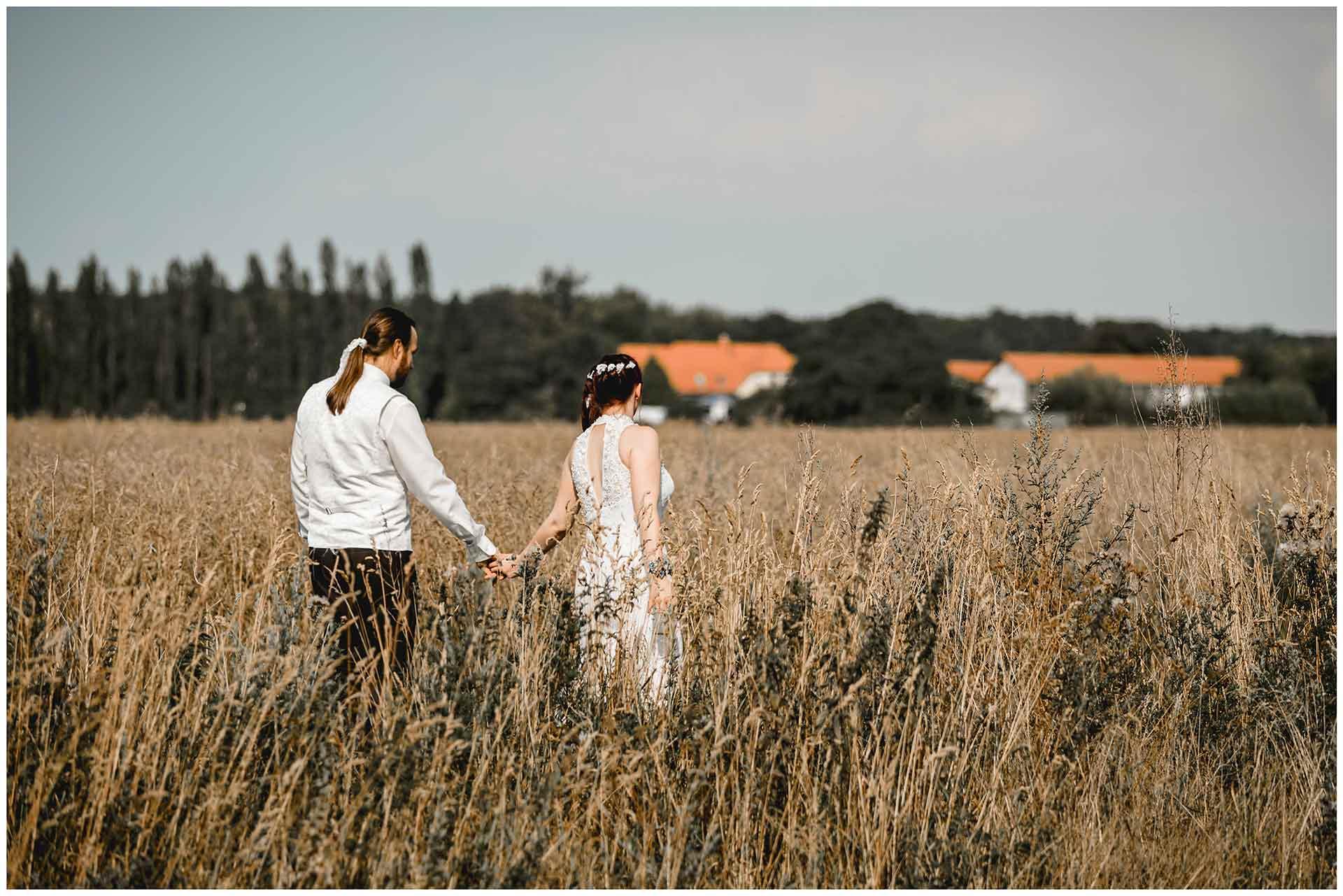 Hochzeitspaar-geht-im-Kornfeld-spazieren-Hochzeitsshooting-Hochzeit-am-Strand-Hochzeitsfotograf-Warnemuende-Hochzeitsfotograf-Rostock-Hochzeitsfotograf-Ostseebad-Warnemuende