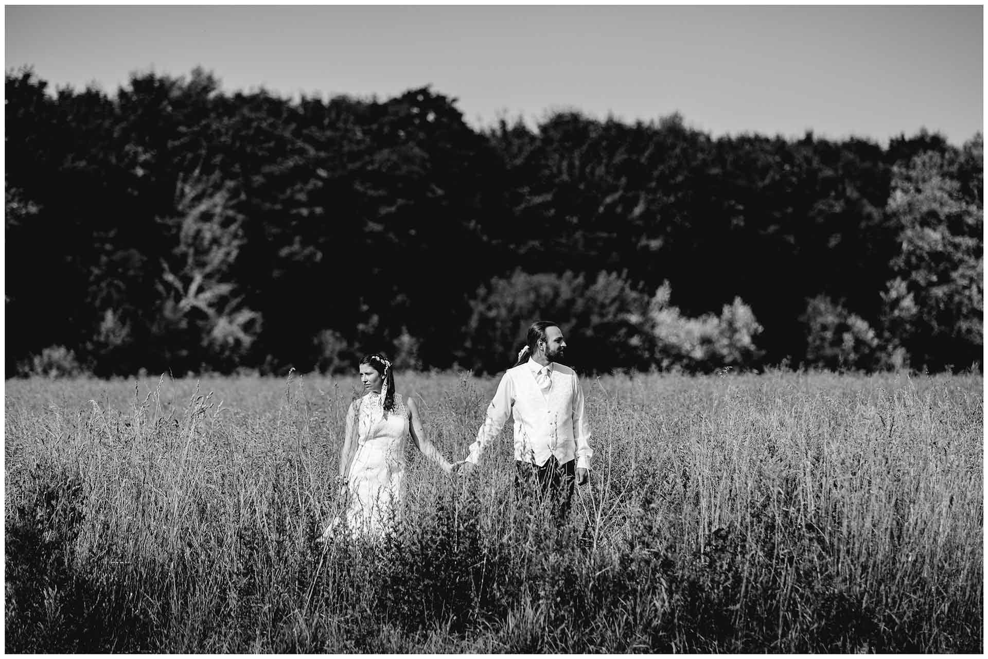 Brautpaar-steht-nebeneinander-auf-einem-Feld-voneinander-wegschauend-Hochzeitsfotografie-Hochzeitsfotograf-Warnemuende-Hochzeitsfotograf-Rostock-Hochzeitsfotograf-Ostseebad-Warnemuende