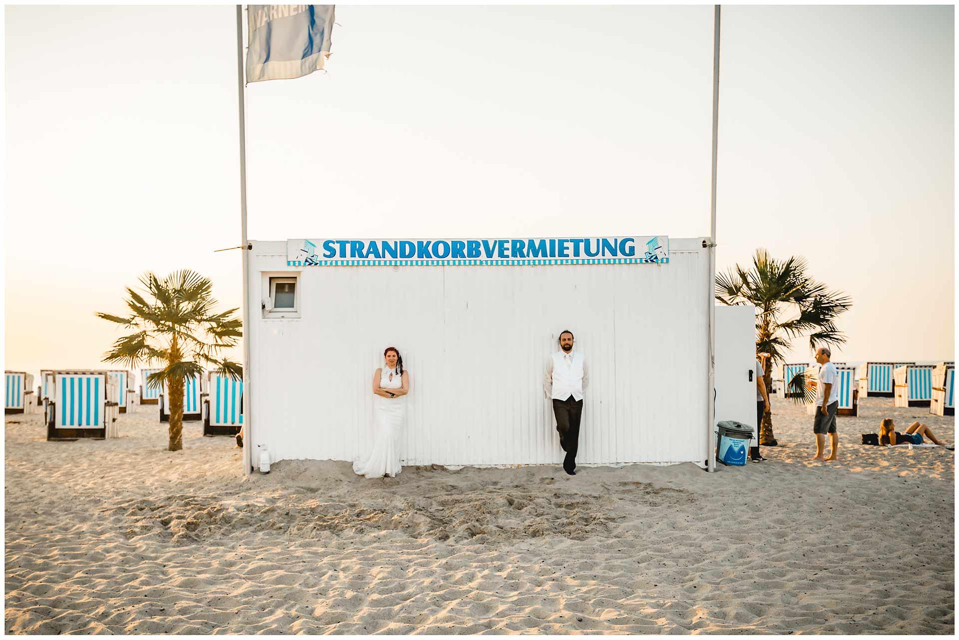 Brautpaar-steht-am-Haus-der-Strandkorbvermietung-Shooting-am-Strand-Hochzeitsfotografie-Hochzeitsfotograf-Warnemuende-Hochzeitsfotograf-Rostock-Hochzeitsfotograf-Ostseebad-Warnemuende