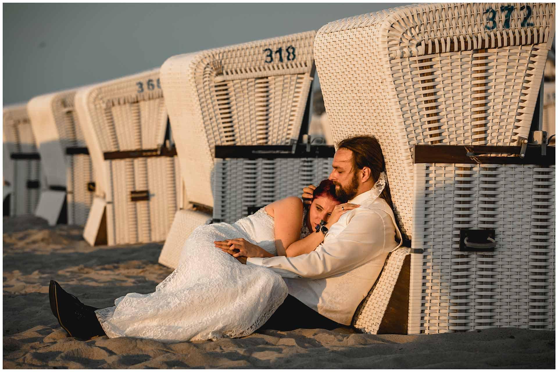 Braut-und-Braeutigam-liegen-eng-umschlungen-an-einen-Strandkorb-gelehnt-Hochzeitsfotografie-Hochzeitsfotograf-Warnemuende-Hochzeitsfotograf-Rostock-Hochzeitsfotograf-Ostseebad-Warnemuende