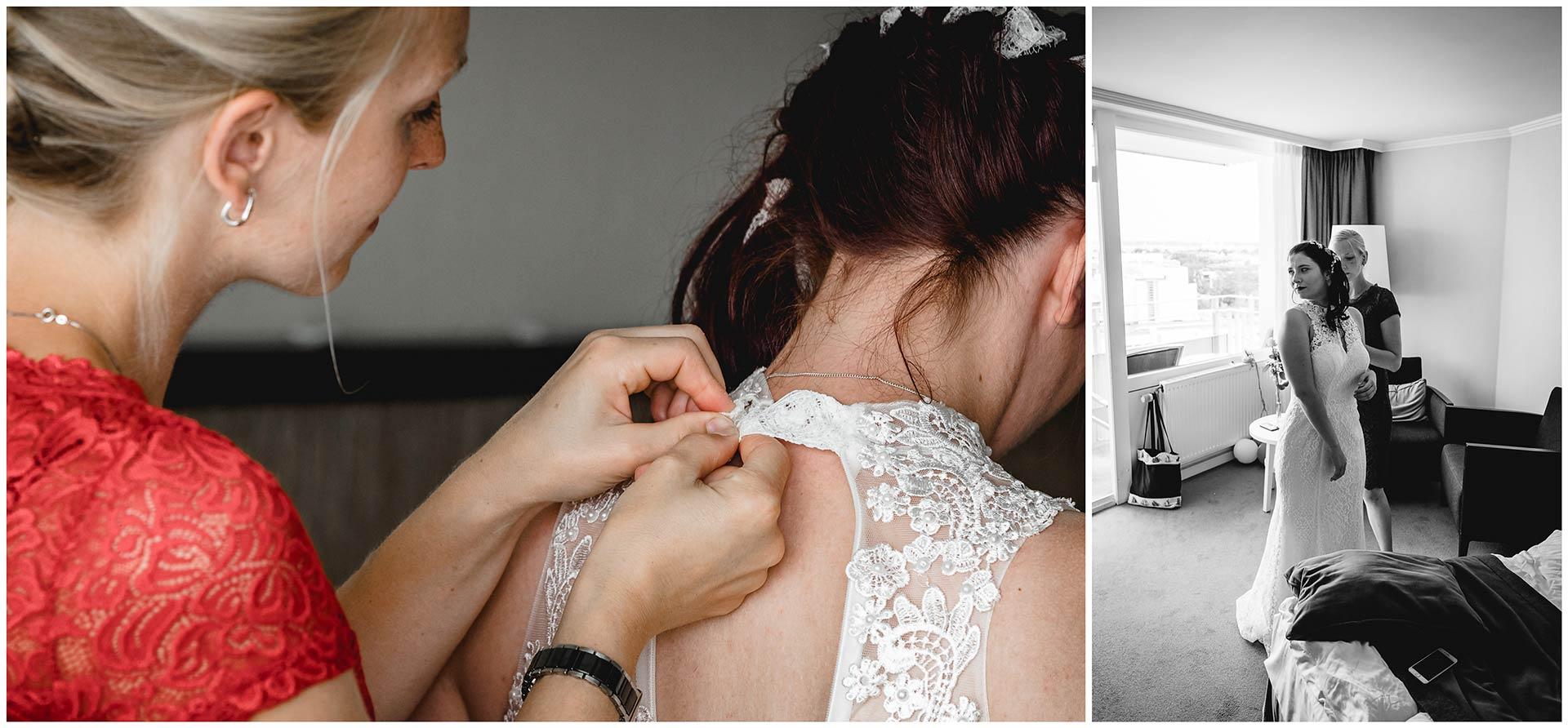 Trauzeugin-hilft-Braut-beim-Ankleiden-macht-Knopf-vom-Hochzeitskleid-zu-Hochzeitsfotograf-Warnemuende-Rostock-Hochzeitsfotograf-Ostseebad-Warnemuende