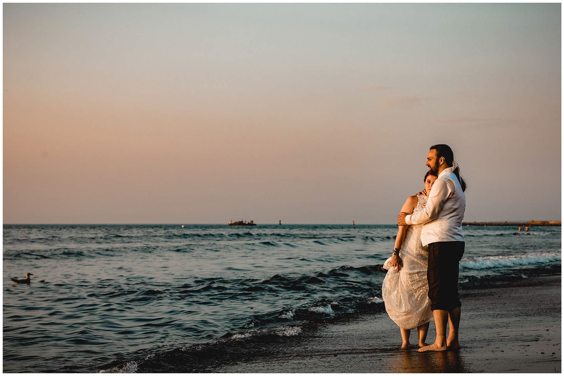 Brautpaar-steht-barfuss-und-arm-in-arm-direkt-an-der-Ostsee-Hochzeitsfotografie-Hochzeitsfotograf-Warnemuende-Hochzeitsfotograf-Rostock-Hochzeitsfotograf-Ostseebad-Warnemuende