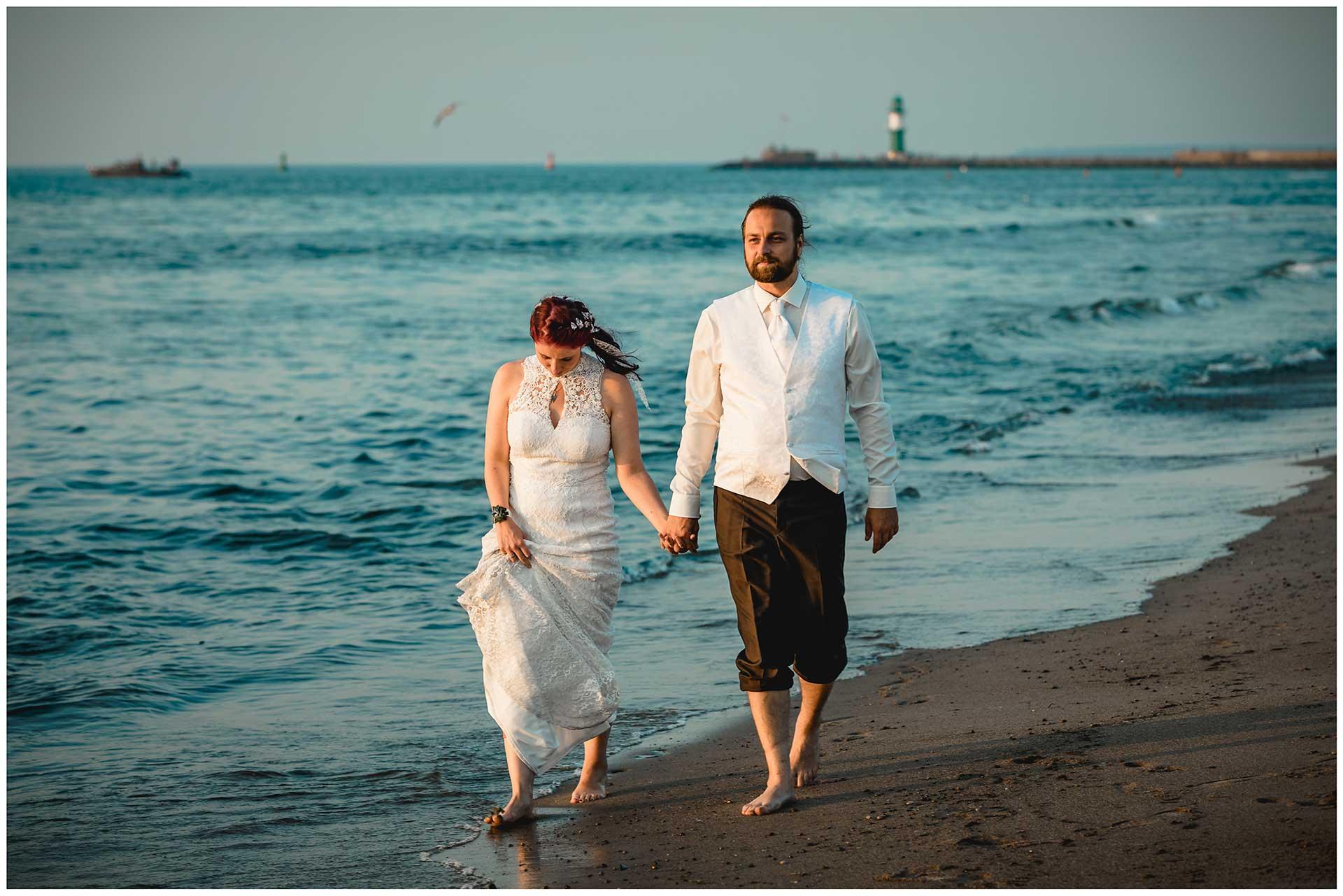 Brautpaar-geht-Barfuss-am-Strand-spazieren-Hochzeitsfotografie-Hochzeitsfotograf-Warnemuende-Hochzeitsfotograf-Rostock-Hochzeitsfotograf-Ostseebad-Warnemuende