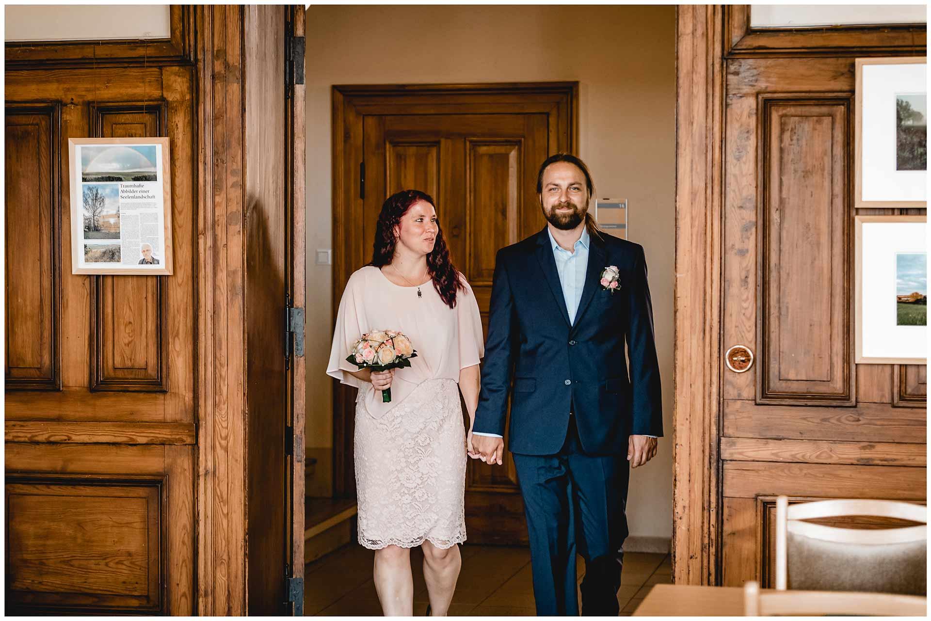 Ehepaar betritt lächelnd den Trausaal im Standesamt Teterow - Hochzeitsfotograf in Teterow