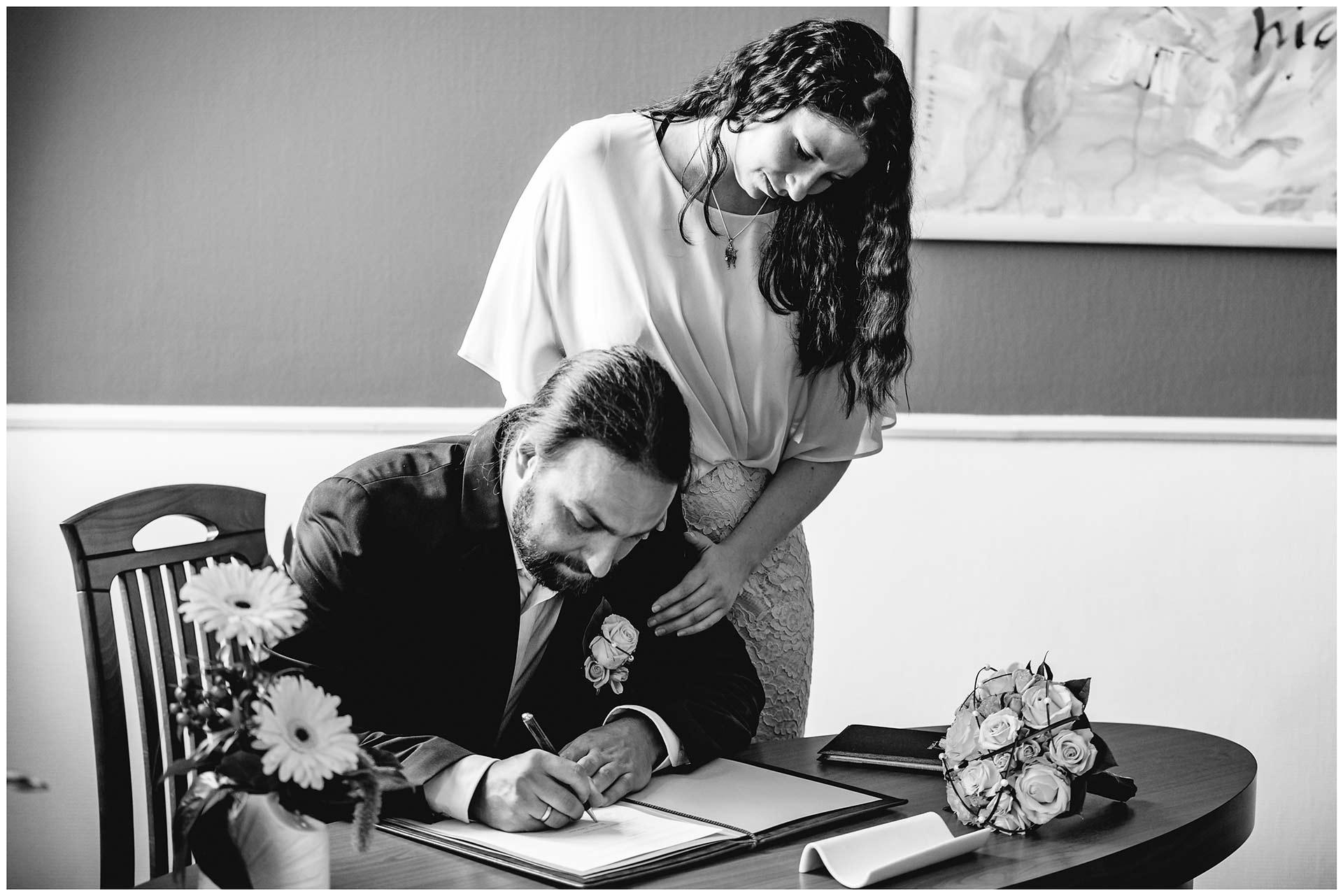 Bräutigam unterschreibt bei der Trauung, Braut steht daneben und hält Bräutigam fest - Hochzeitsfotograf in Teterow