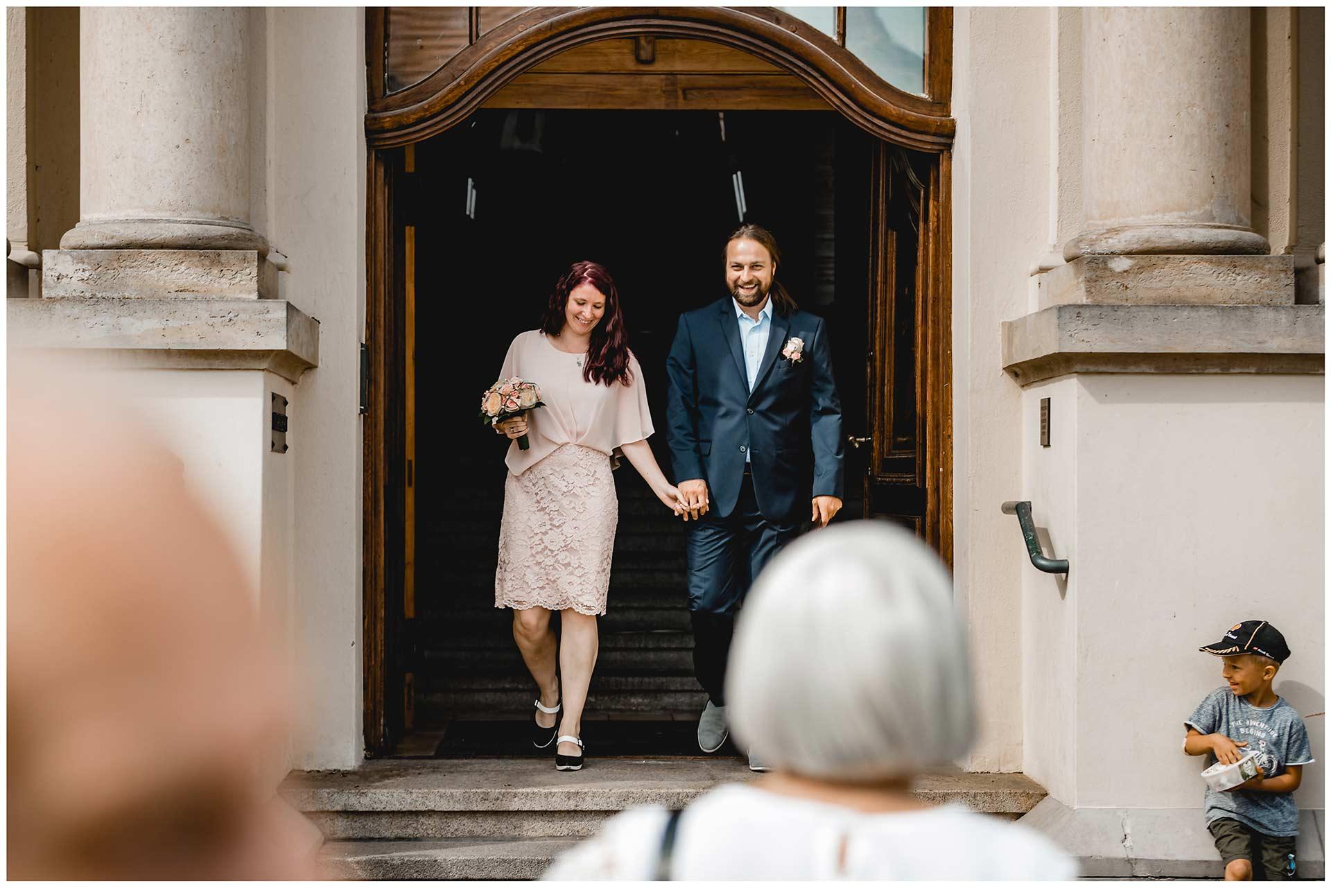 Brautpaar kommt lachend nach der Trauung aus dem Rathaus Teterow - Hochzeitsfotograf in Teterow