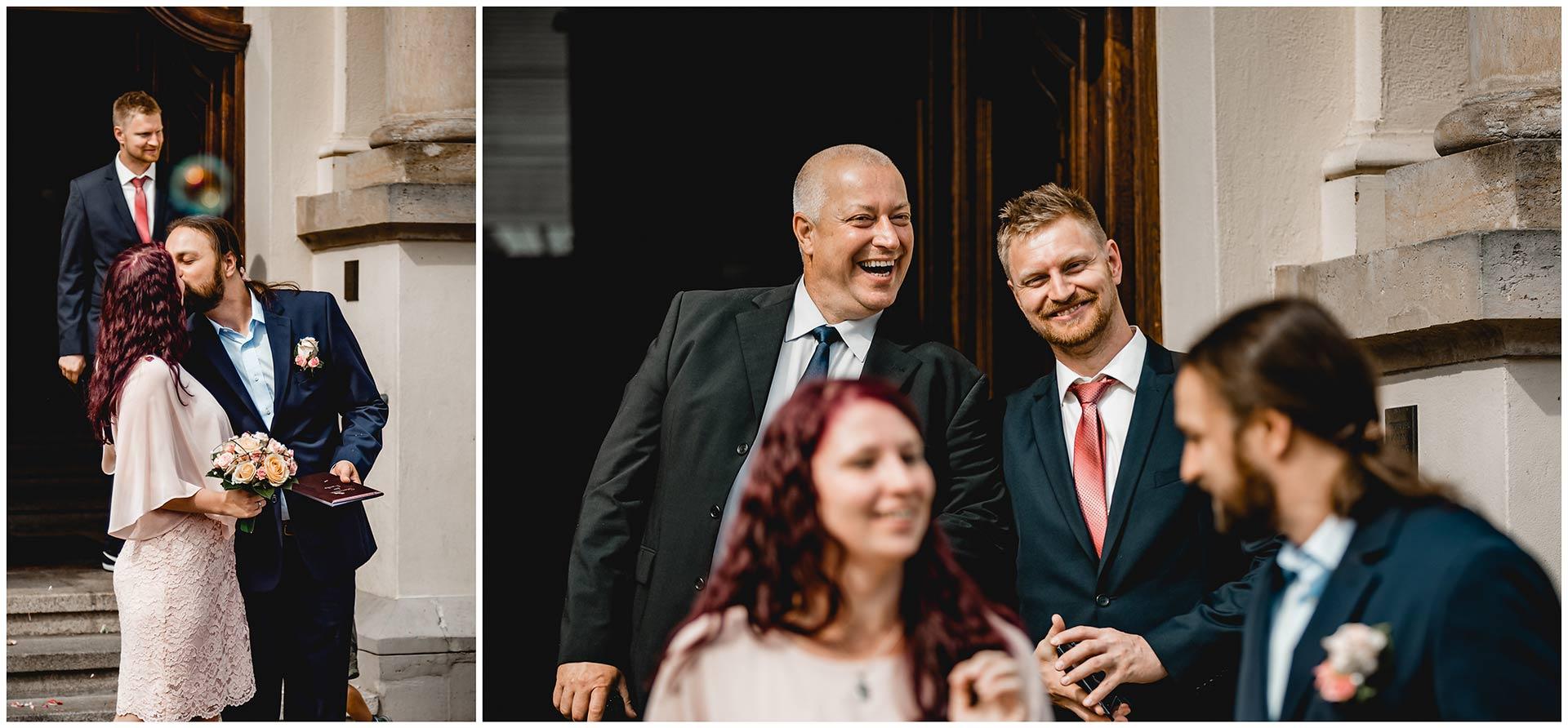 Braut küsst Bräutigam, Hochzeitsgäste lachen hinter dem Brautpaar - Hochzeitsfotograf in Teterow