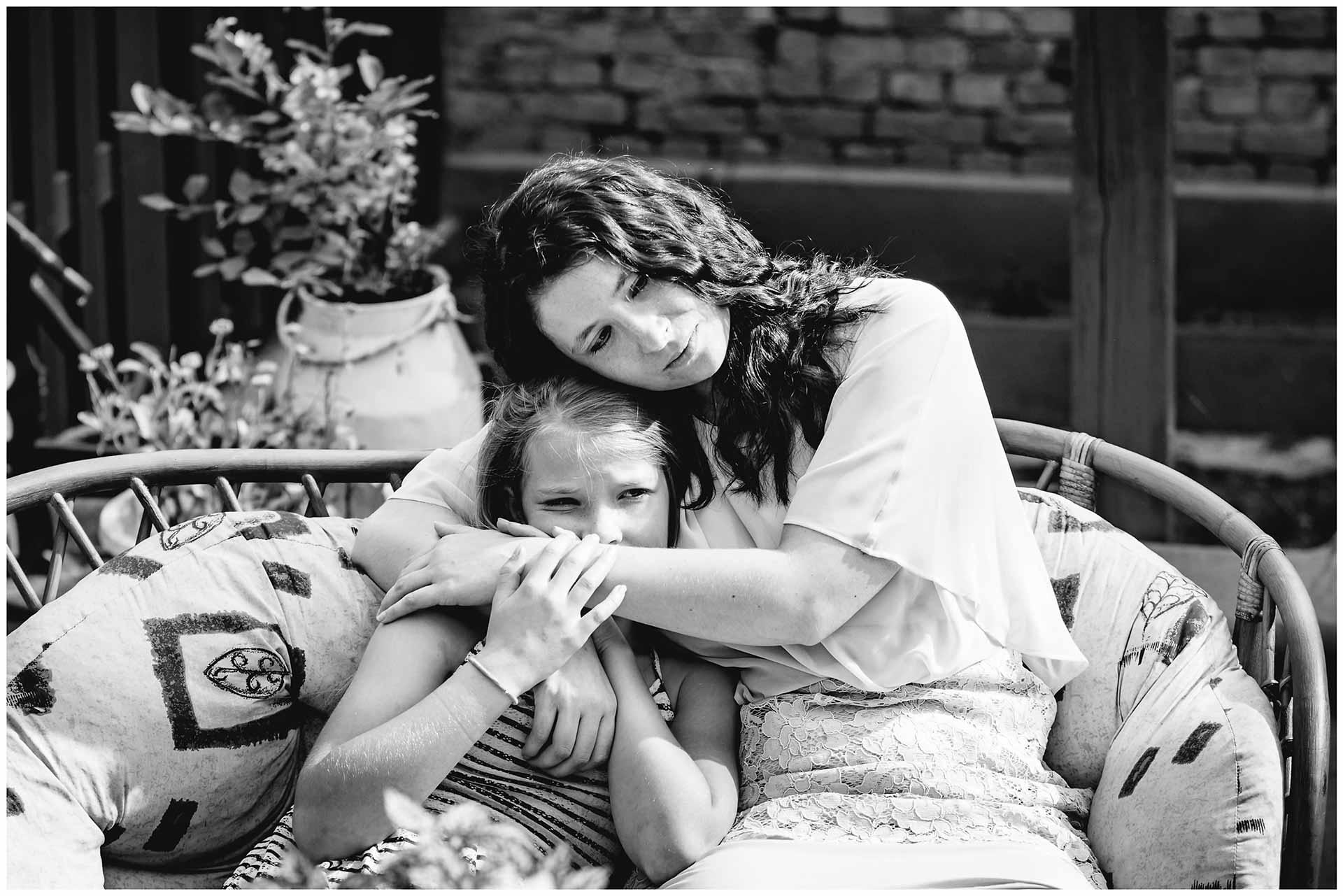 Braut sitzt mit kleinem Mädchen arm in arm - Hochzeitsfotograf Teterow