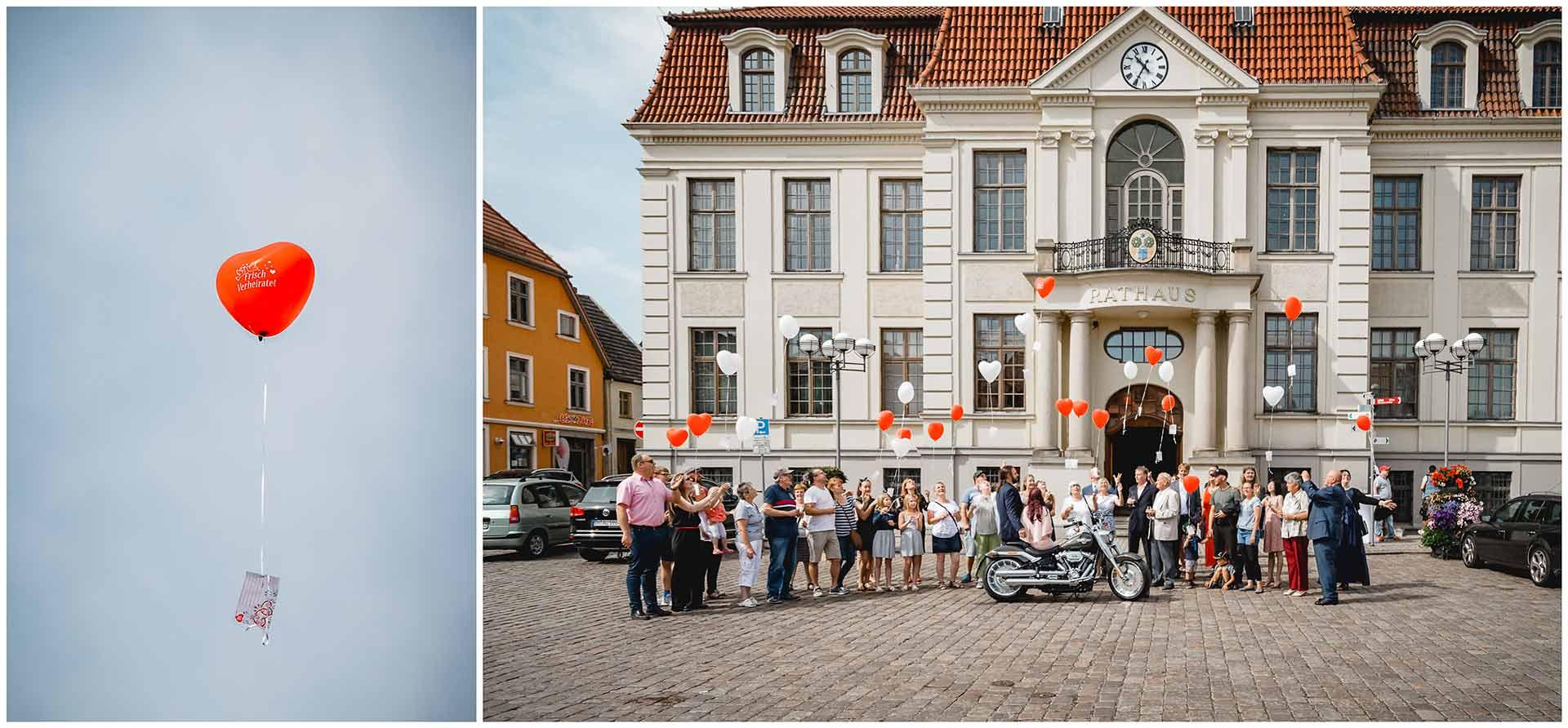 Hochzeitsgäste vor dem Rathaus Teterow lassen Luftballons steigen - Hochzeitsfotograf in Teterow