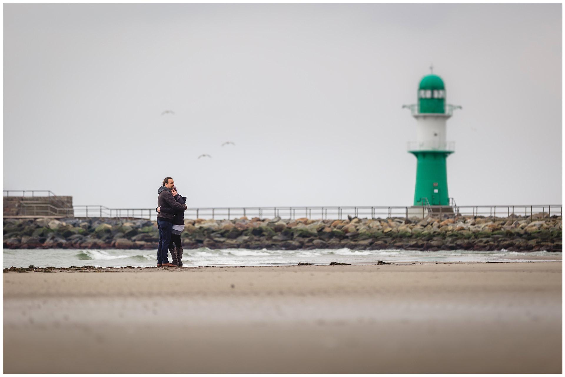 weitwinkelaufnahme-paar-eng-umarmt-steht-am-ostseestrand-im-hintergrund-moewen-und-leuchtturm-mole-warnemuende-shooting-am-strand-fotoshooting-paerchenbilder-fotograf-warnemuende-fotograf-rostock