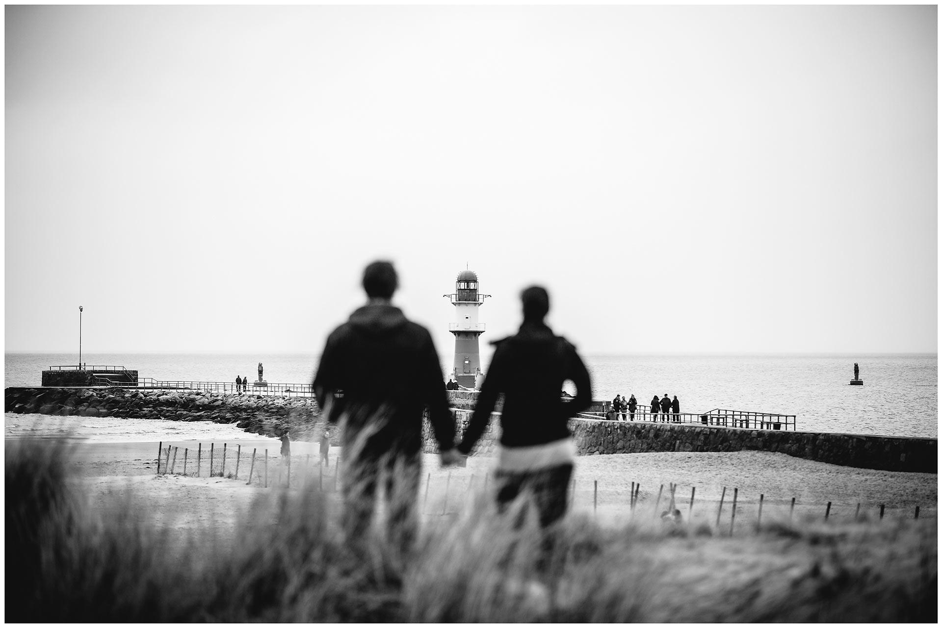 paar-steht-hand-in-hand-auf-duenen-am-strand-schaut-richtung-leuchtturm-warnemuender-mole-shooting-am-strand-paarshooting-fotograf-rostock-fotograf-warnemünde-paerchenbilder-fotoshooting