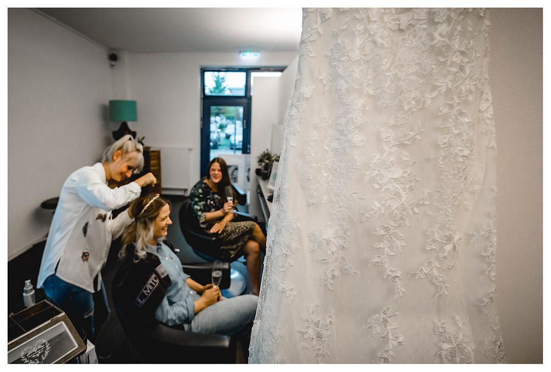 Vordergrund-Detailaufnahme-Hochzeitskleid-Hintergrund-Braut-Friseurun-Schwester - Fotograf Rostock