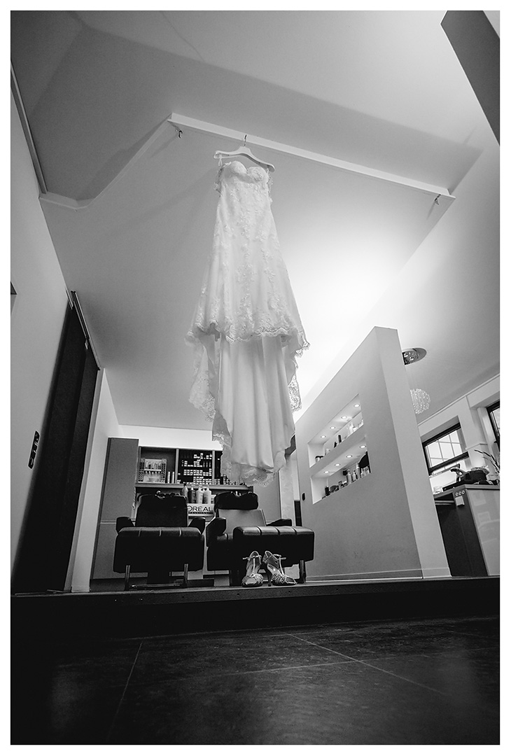 Hochzeitsfotograf Rostock - Hochzeitskleid-haengt-auf-Buegel-im-Friseurladen-darunter-stehen-Brautschuhe - Fotograf Rostock - Hochzeitsfotograf Villa Papendorf