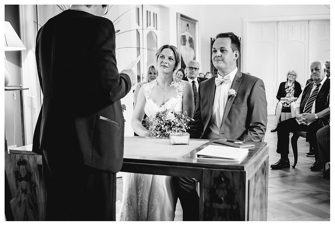 Hochzeitsfotograf Rostock - Brautpaar sitzend vor Standesbeamtin - Fotograf Rostock - Hochzeitsfotograf Villa Papendorf