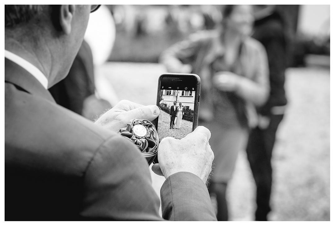 Hochzeitsfotograf - Nahaufnahme Handy - Gast fotografiert Brautpaar - Hochzeitsfotograf Villa Papendorf