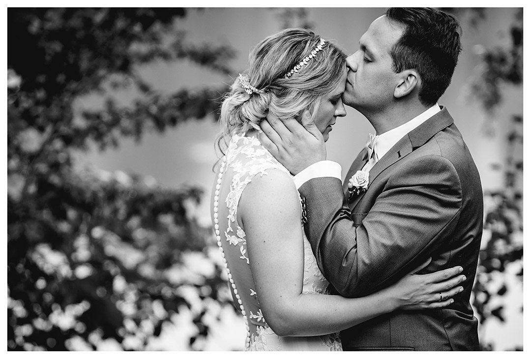 Hochzeitsfotograf Rostock - Brautpaarshooting - Bräutigam küsst Braut auf Stirn - Fotograf Rostock - Hochzeitsfotograf Villa Papendorf