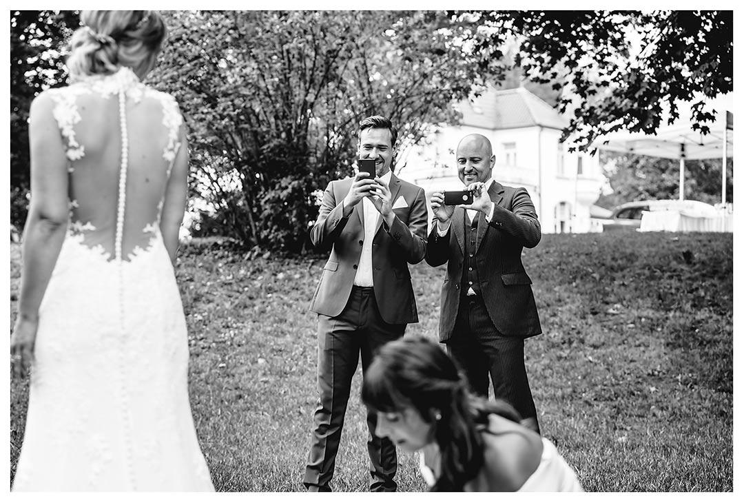 Hochzeitsfotograf - zwei Männer fotografieren mit Handy wie Kleid der Braut gerichtet wird - Hochzeitsfotograf Villa Papendorf
