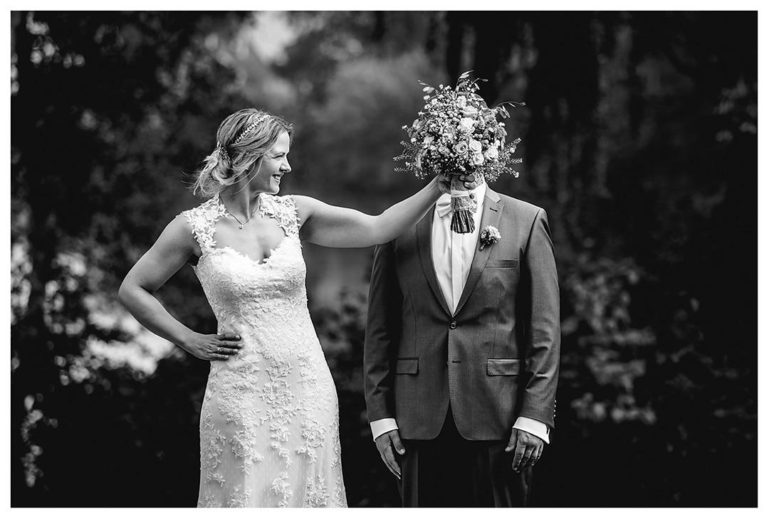 Hochzeitsfotograf Rostock - Brautpaarshooting - Braut hält lachend Brautstrauß vor Gesicht des Bräutigams - Fotograf Rostock - Hochzeitsfotograf Villa Papendorf