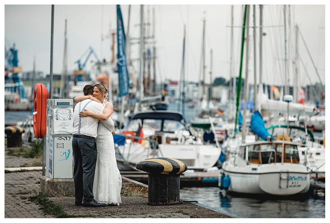 Brautpaar eng umarmt-im Hintergrund Segelboote - Stadhafen - Warnowufer - Hochzeitsfotos