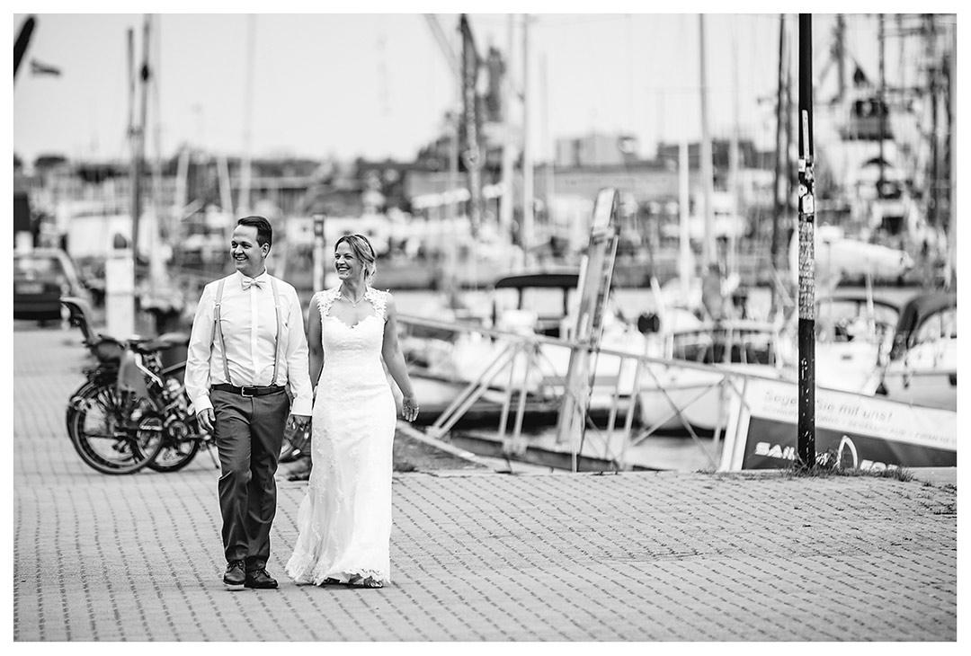 Hochzeitsfotograf Rostock - Brautpaar geht lächelnd Hand in Hand - Stadthafen - Warnowufer - Hochzeitsfotos