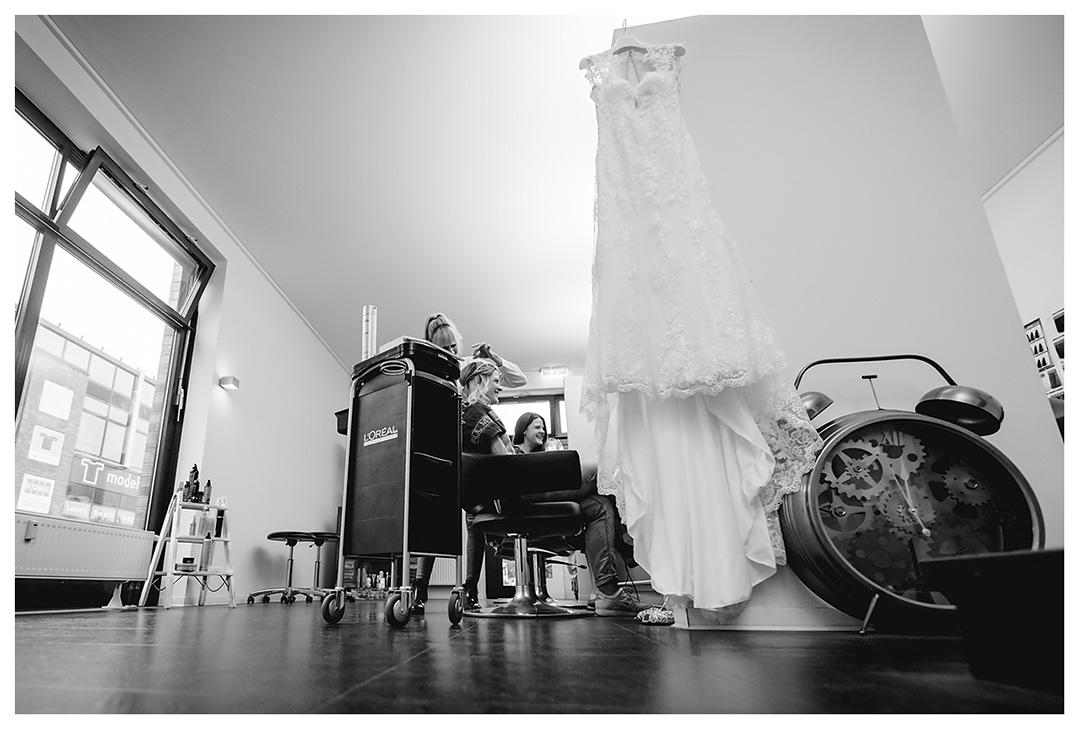 Hochzeitsfotograf Rostock - Braut-wird-frisiert-im-Vordergrund-haengt-das-Hochzeitskleid - Fotograf Rostock - Hochzeitsfotograf Villa Papendorf