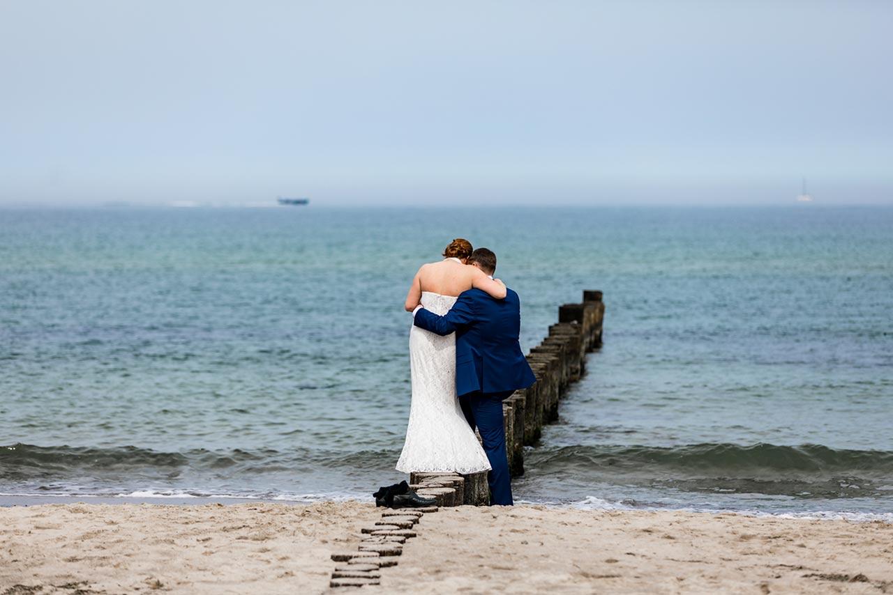 Brautpaar steht eng zusammen direkt am Wasser der Ostsee - Hochzeitsfotos - Fotograf Rostock Hochzeit