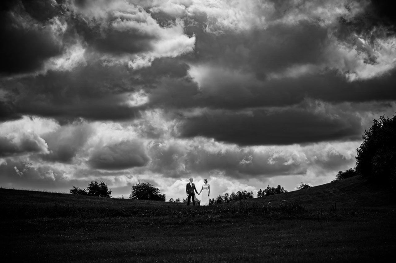 Weitwinkelaufnahme Brautpaar über ihnen viele Wolken - Hochzeitsfotos - Fotograf Rostock Hochzeit