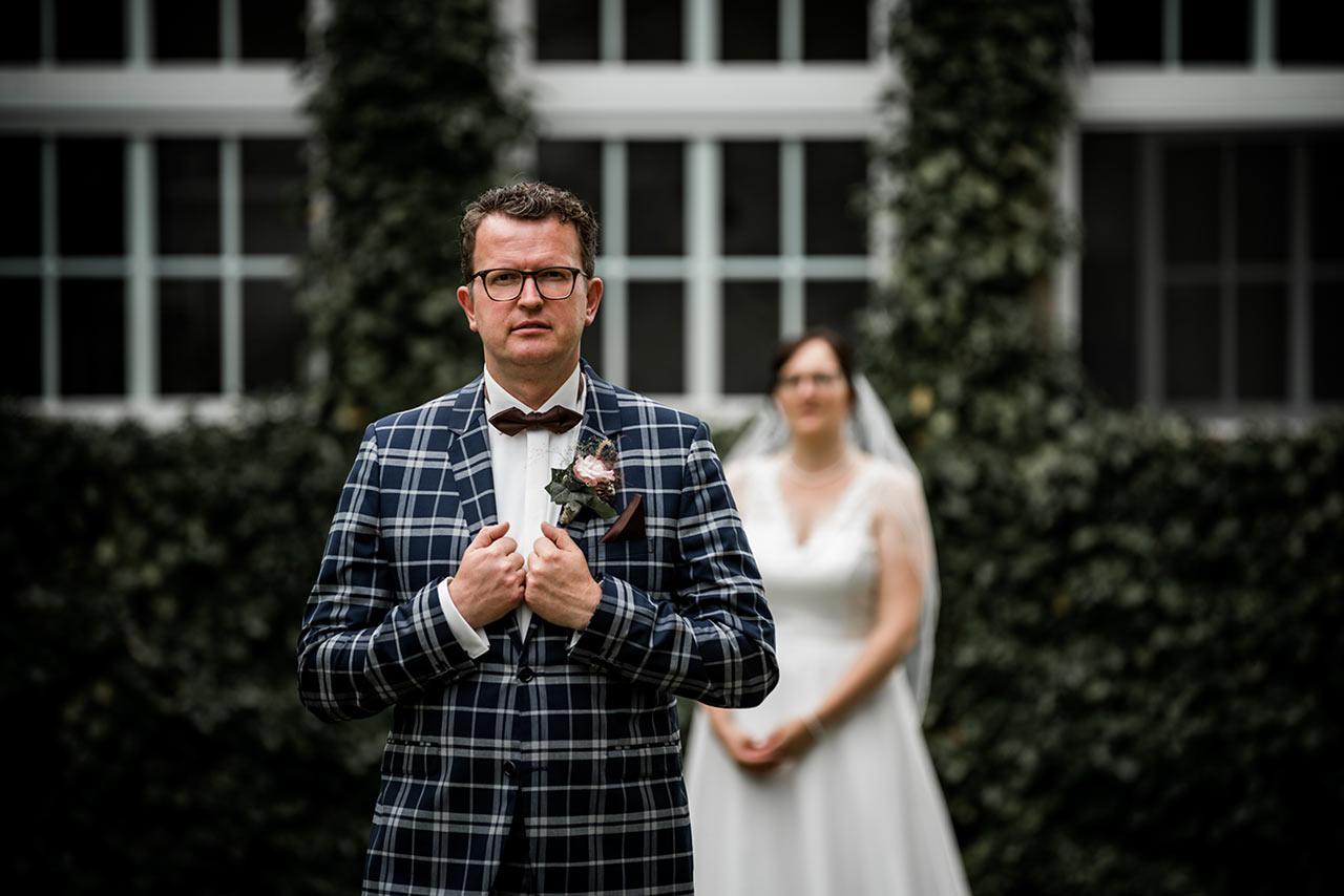 Brautpaar - im Vordergrund steht der Bräutigam - Hochzeitsfotos - Fotograf Rostock Hochzeit