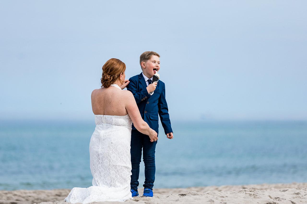 Braut kniet vor ihrem Sohn der ein Eis leckt - Hochzeitsfotos - Fotograf Rostock Hochzeit