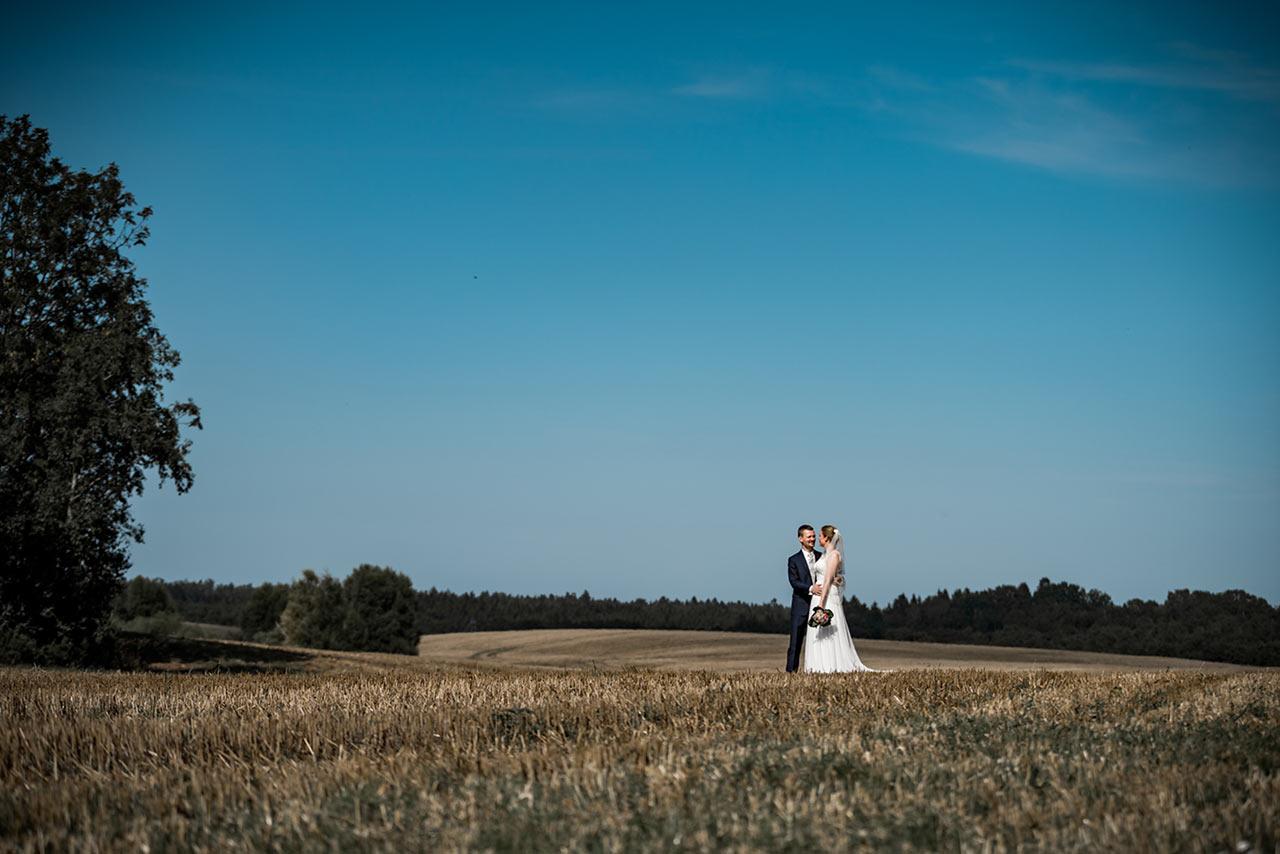 Brautpaar Arm in Arm auf einem abgemähten Feld - Hochzeitsfotos - Fotograf Rostock Hochzeit