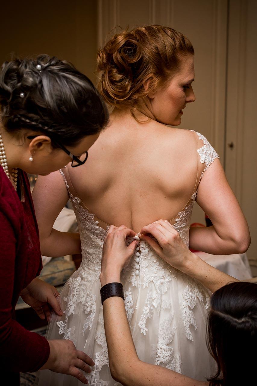 Freundin und Trauzeugin der Braut knöpfen Kleid zu - Hochzeitsfotograf Bredenfelde