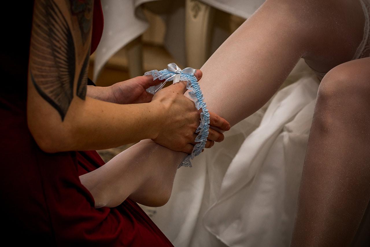Blaues Strumpfband wird über Bein der Braut gestreift - Fotograf Bredenfelde