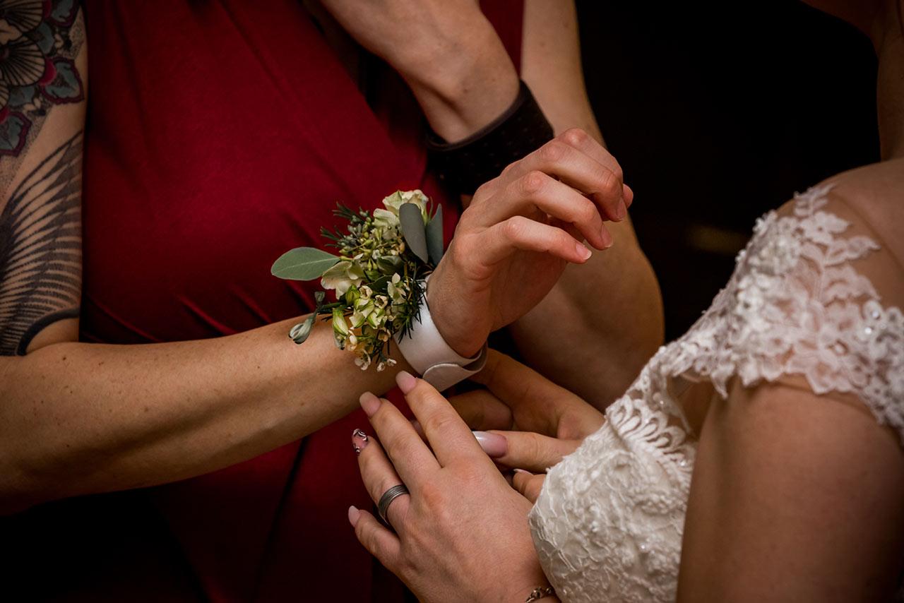 Braut legt Trauzeugin Blumenarmband an - Fotograf Hochzeit Schloss Bredenfelde