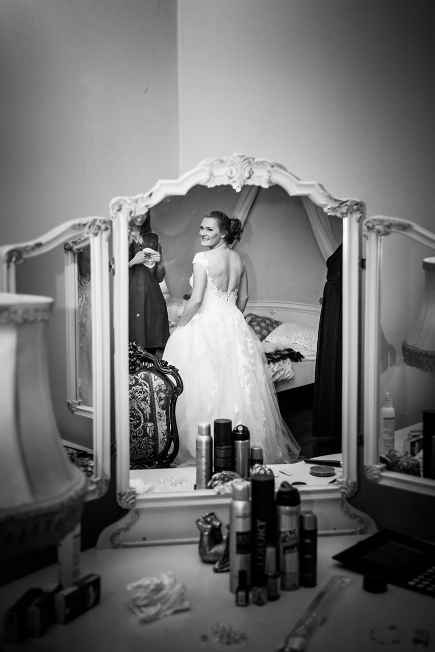 Braut ist lächelnd im Spiegel zu sehen - Hochzeitsfotograf Bredenfelde