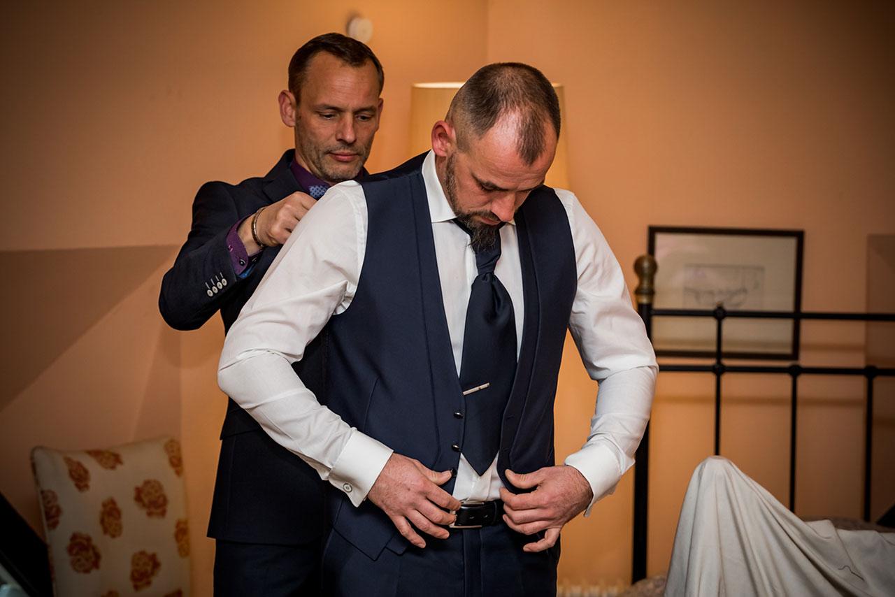 Bräutigam zieht Anzugweste an und Trauzeuge hilft ihm - Hochzeitsfotograf Bredenfelde