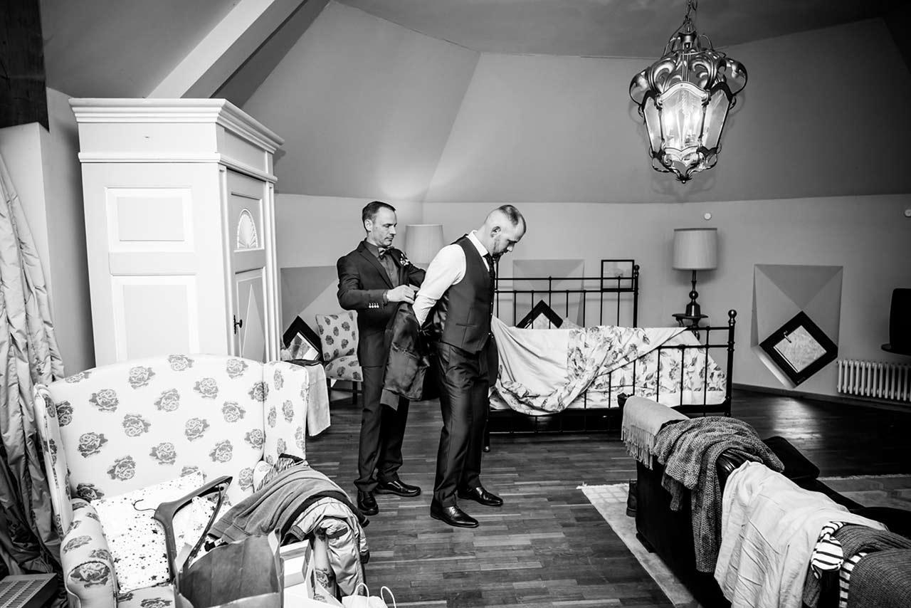 Weitwinkelaufnahme Trauzeuge hilft Bräutigam in Sacko anzuziehen - Hochzeitsfotograf Bredenfelde
