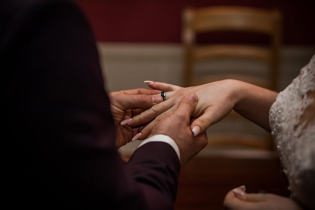 Bräutigam steck Ehering auf Finger der Braut - Hochzeitsfotograf