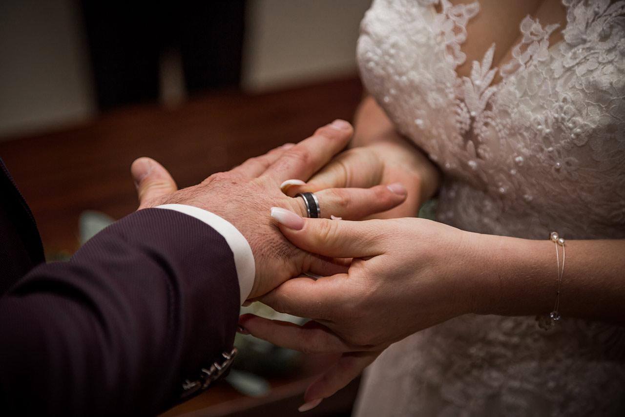 Braut steck Ehering auf Finger des Bräutigams - Hochzeitsfotograf Bredenfelde