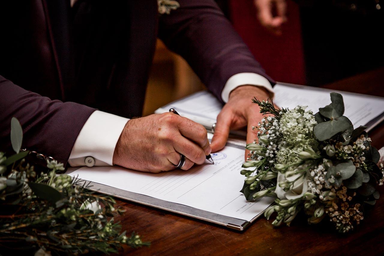 Nahaufnahme Bräutigam unterschreibt Eheurkunde - Hochzeitsfotograf Rostock