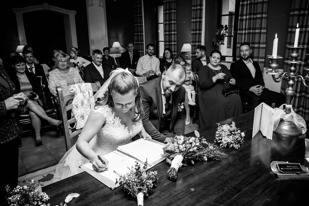 Bräutigam schaut Braut beim unterschreiben der Eheurkunde zu - Hochzeitsfotograf Bredenfelde