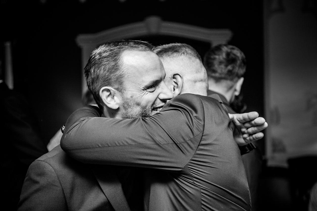 Trauzeuge umarmt Bräutigam nach Trauung - Hochzeitsfotograf Rostock