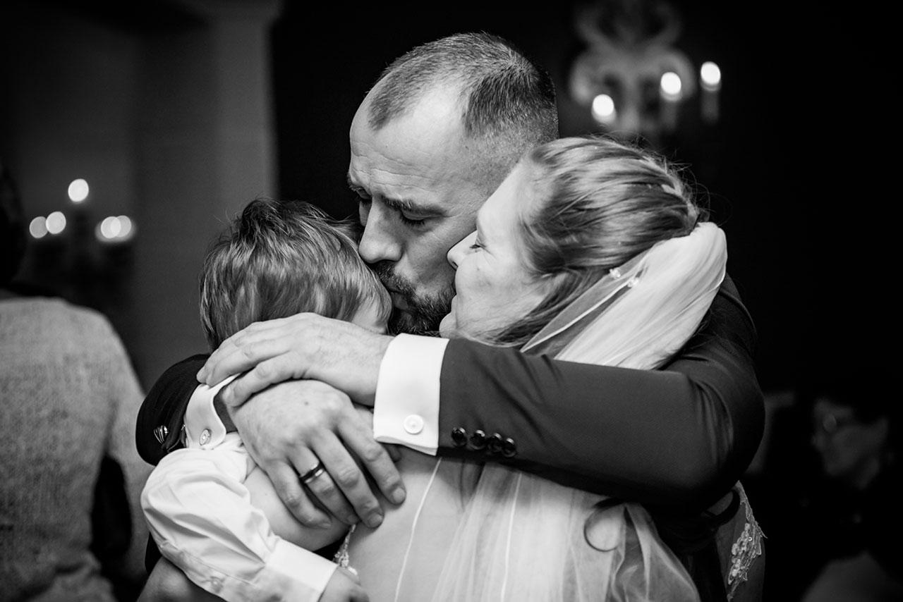 Brautpaar umarmt zusammen ihren kleinen Sohn - Bräutigam küsst kleinen Sohn auf die Stirn - Hochzeitsfotograf Bredenfelde