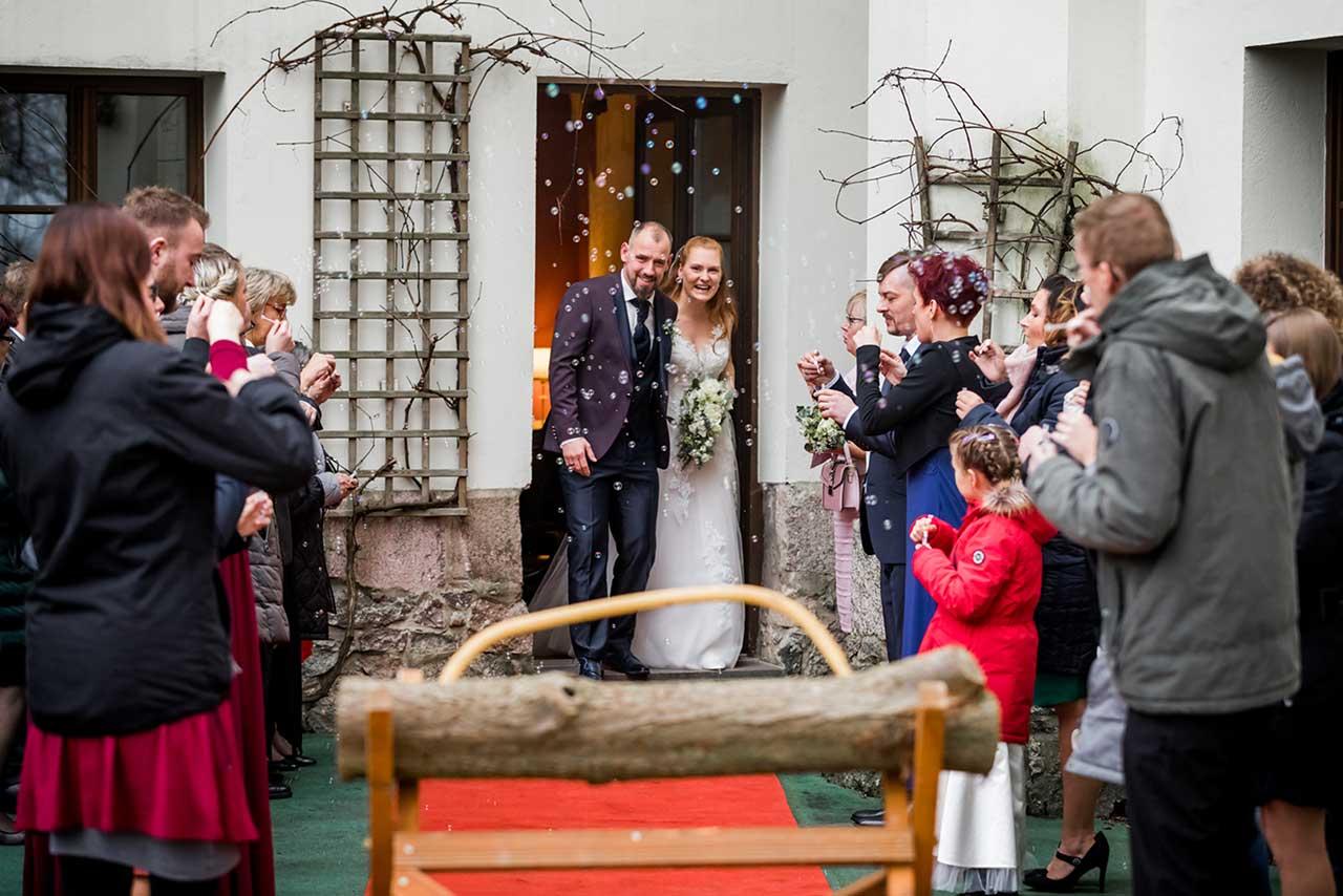 Hochzeitspaar kommt aus Tür im Vordergrund Baumstamm zum sägen - Hochzeitsfotograf