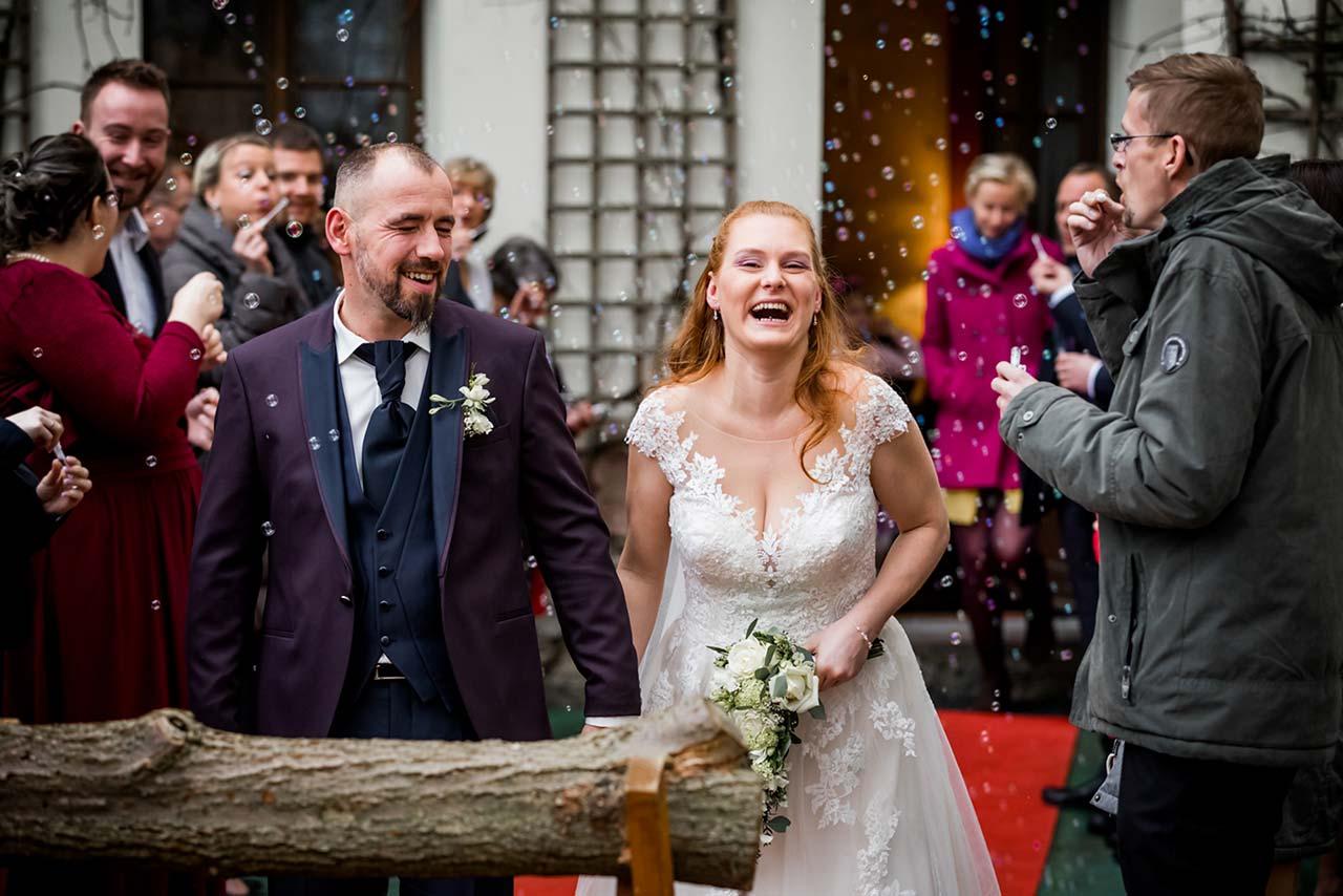 Brautpaar lächt herzlich - im Vordergrund Baumstamm zum sägen - Hochzeitsfotograf