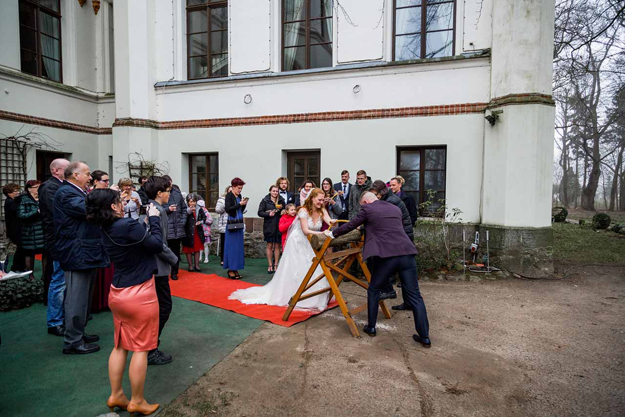 Hochzeitspaar beim Baumstamm sägen im Hintergrund Hochzeitsgäste - Hochzeitsfotograf