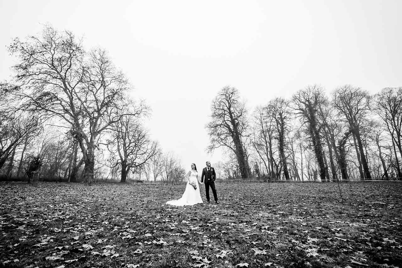 Weitwinkelaufnahme Brautpaar steht auf Wiese - Hochzeitsshooting - Hochzeitsfotografie - Hochzeitsfotograf Bredenfelde