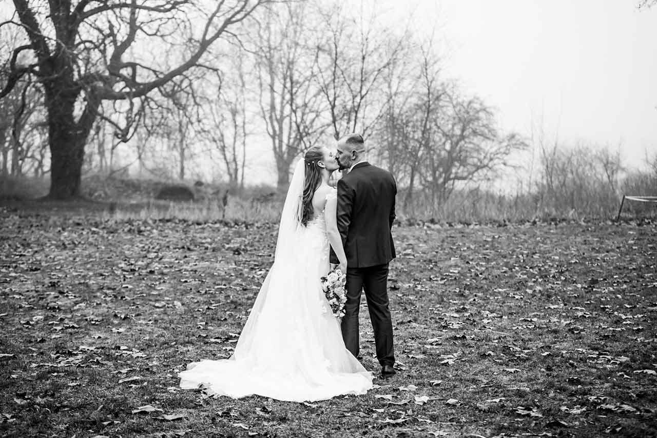 Brautpaar von hinten zu sehen küsst sich und steht auf Wiese - Hochzeitsshooting - Hochzeitsfotografie - Hochzeitsfotograf Bredenfelde