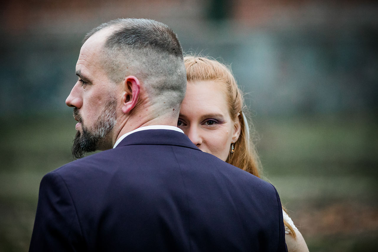 Nahaufnahme Braut schaut über Schulter des Bräutigams - Hochzeitsshooting - Hochzeitsfotografie - Hochzeitsfotograf Bredenfelde