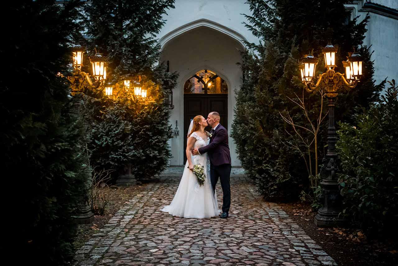 Brautpaar Arm in Arm und küsst sich vor Eingang Schloss Bredenfelde abendlich Stimmung - Hochzeitsfotograf Bredenfelde