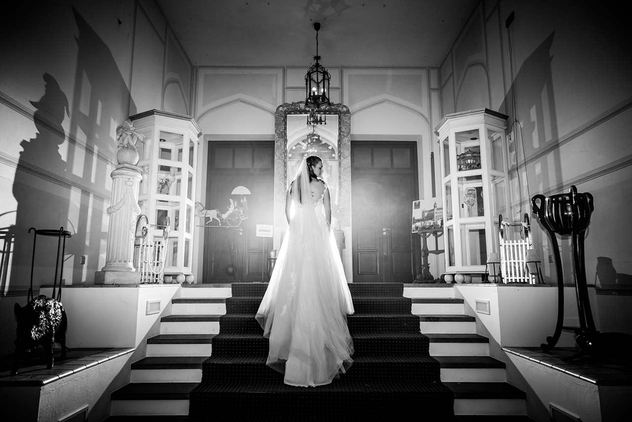 Braut von hinten zu sehen steht auf Treppe Eingangsbereich Schloss Bredenfelde - Hochzeitsfotograf Bredenfelde